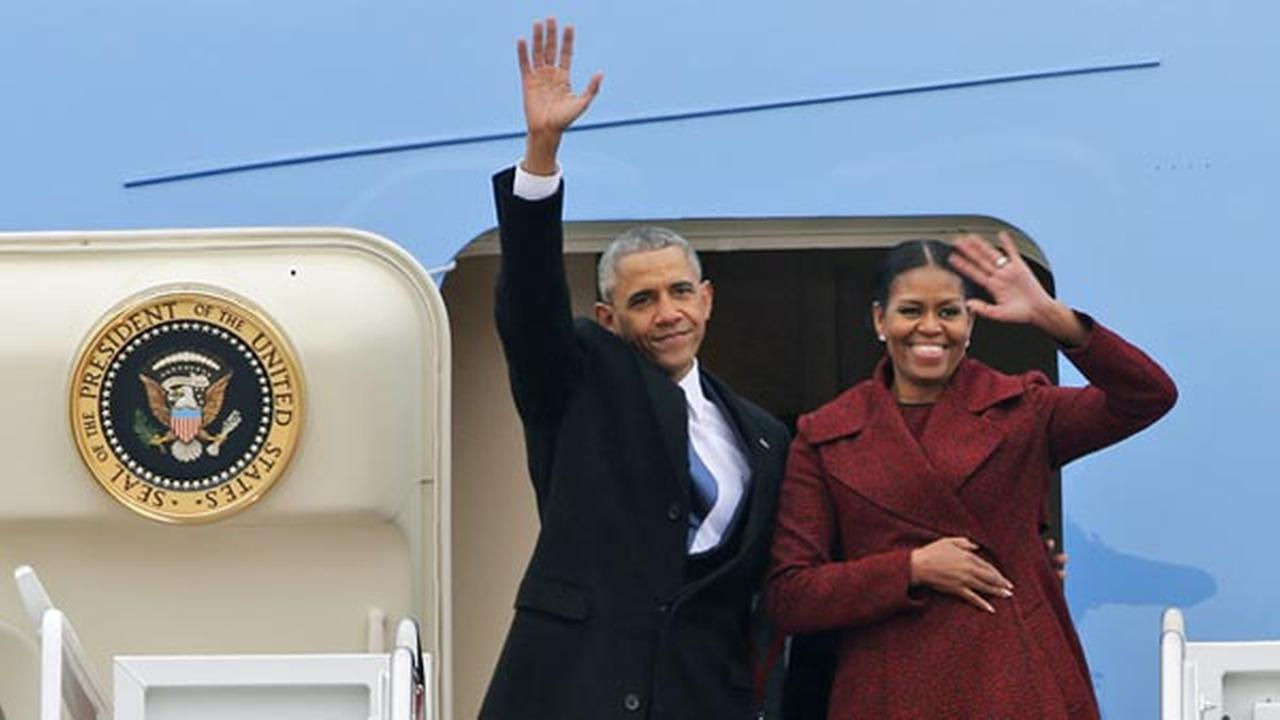 Former President Barack Obama and his wife Michelle wave to the crowd as they board an Air Force jet to depart Andrews Air Force base in Andrews Air Force Base Md