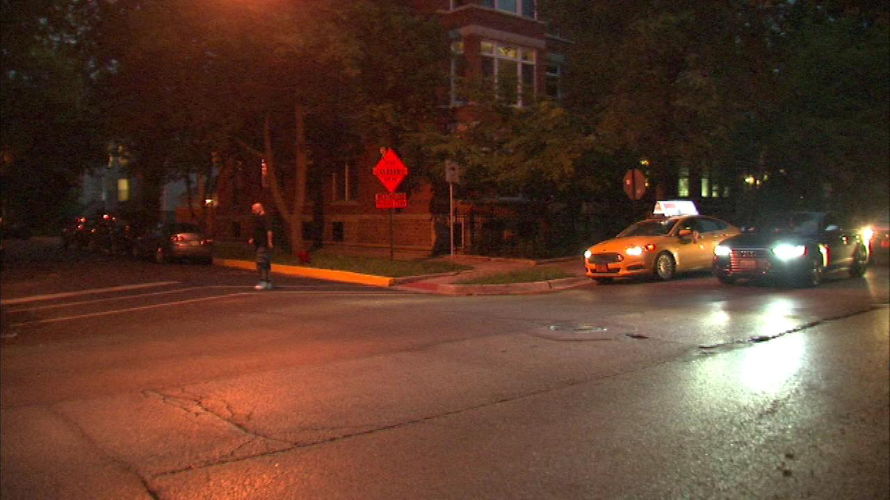 A woman in her 20s was robbed in Lincoln Park by a gunman who had a semi-automatic weapon.
