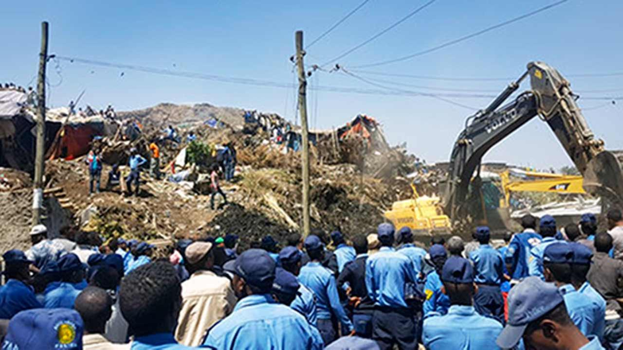 Police officers secure the perimeter at the scene of a garbage landslide, as excavators aid rescue efforts, on the outskirts of the capital Addis Ababa, Ethiopia Sunday, March 12,
