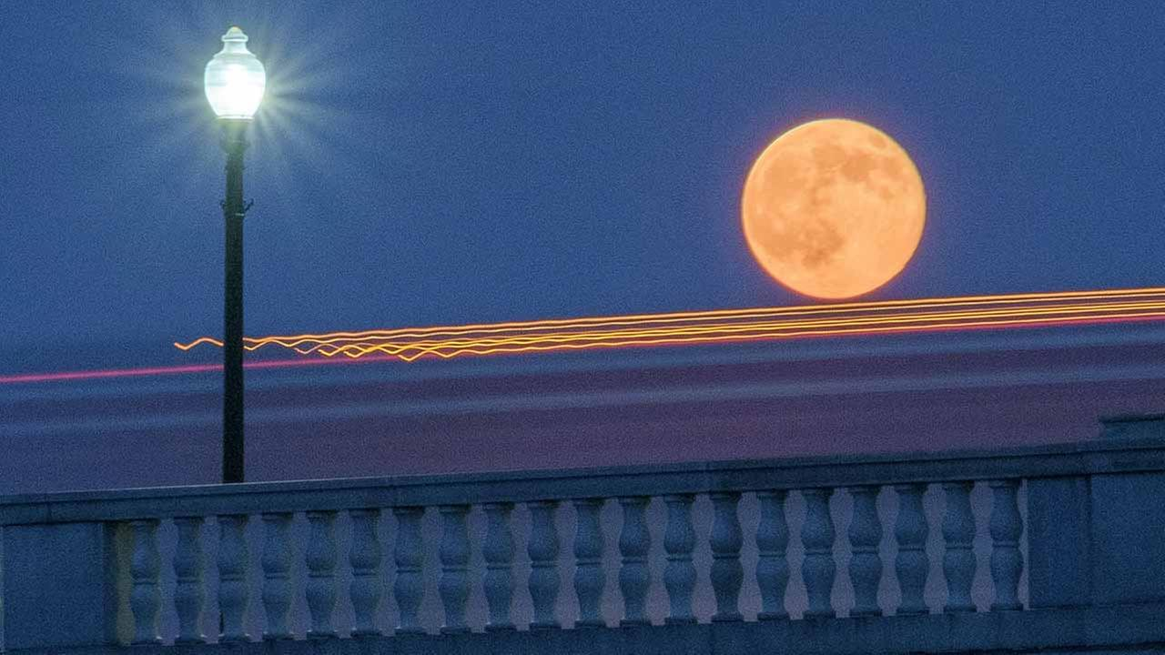 Traffic streaks by the supermoon as it rises behind the Memorial Bridge in Washington, Saturday, July 12, 2014.