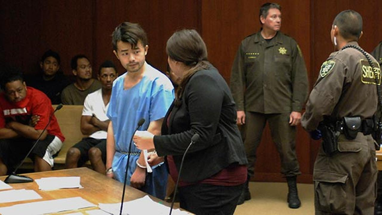 Yu Wei Gong, left, speaks to Deputy Public Defender Diamond Grace in court in Honolulu on Monday, April 17, 2017.  He is accused of murdering his mother and hiding her body parts.