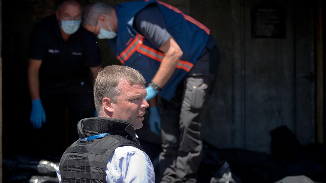 Deputy head of the OSCE mission to Ukraine Alexander Hug stands outside a refrigerated train, as members of Netherlands National Forensic Investigations Team inspect bodies.