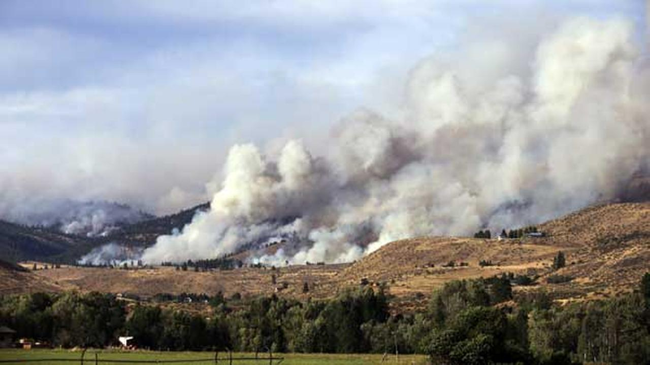 Clouds of smoke billow from a wildfire near Twisp, Wash. A fire racing through rural north-central Washington destroyed about 100 homes as it blackened hundreds of square miles.