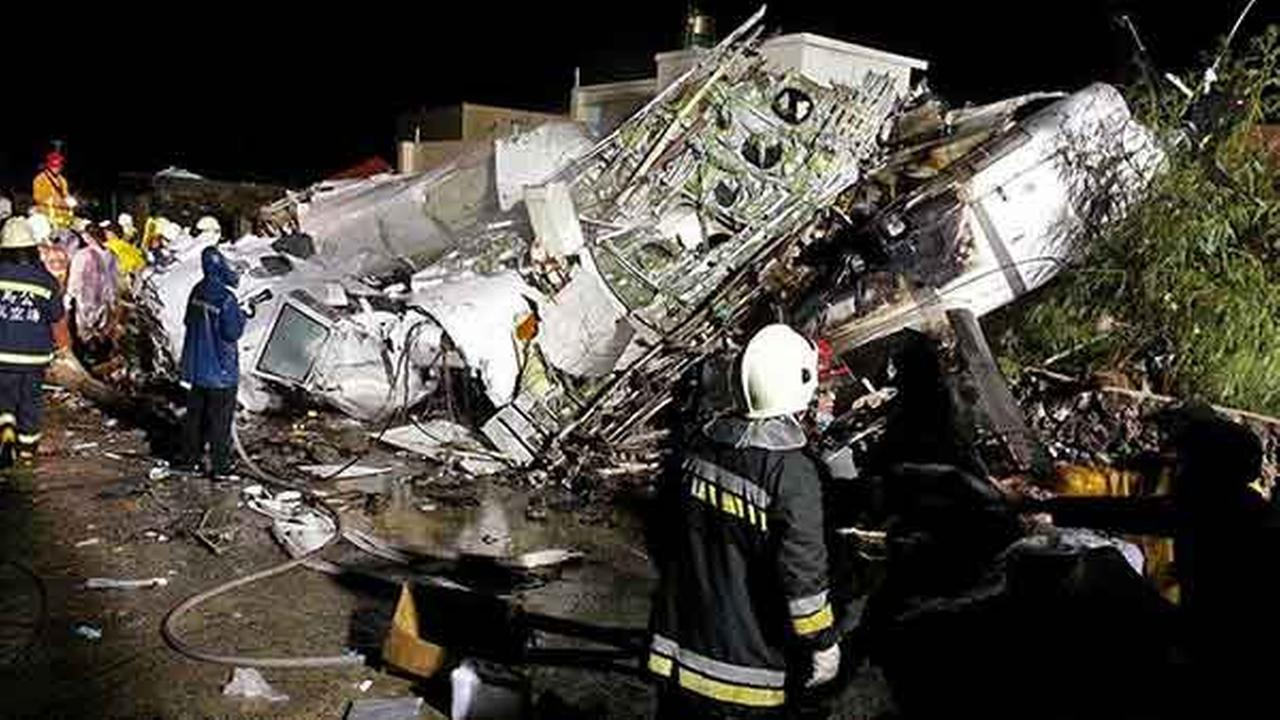 Rescue workers survey the wreckage of TransAsia Airways flight GE222, which crashed while attempting to land in stormy weather on the Taiwanese island of Penghu on July 23, 2014.
