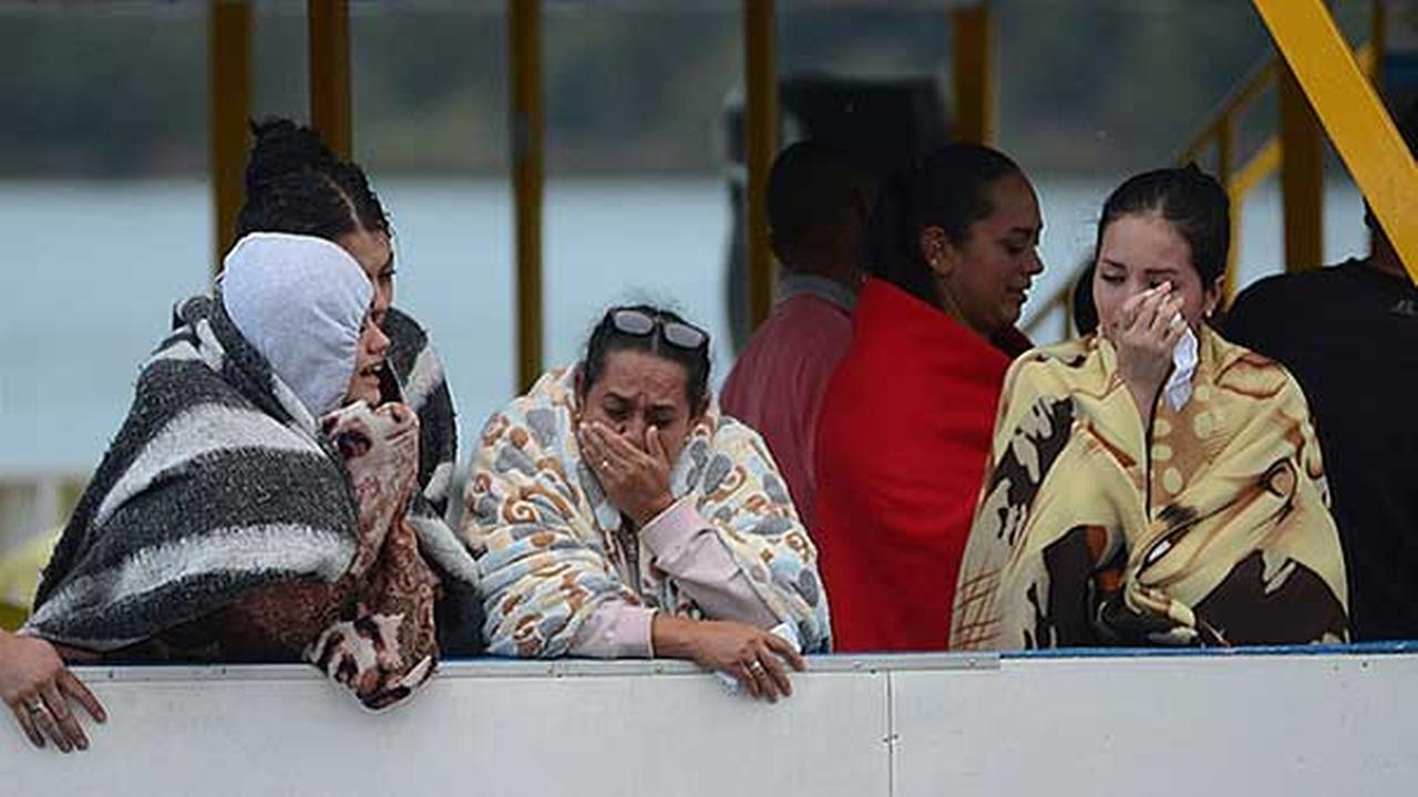 People cry as they wait for more information on tourists who were on a ferry that sank in a reservoir in Guatape, Colombia.