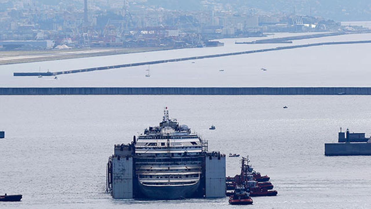 The wreck of the Costa Concordia cruise ship is towed by tugboats towards Genoas harbor, Italy, Sunday, July 27, 2014.
