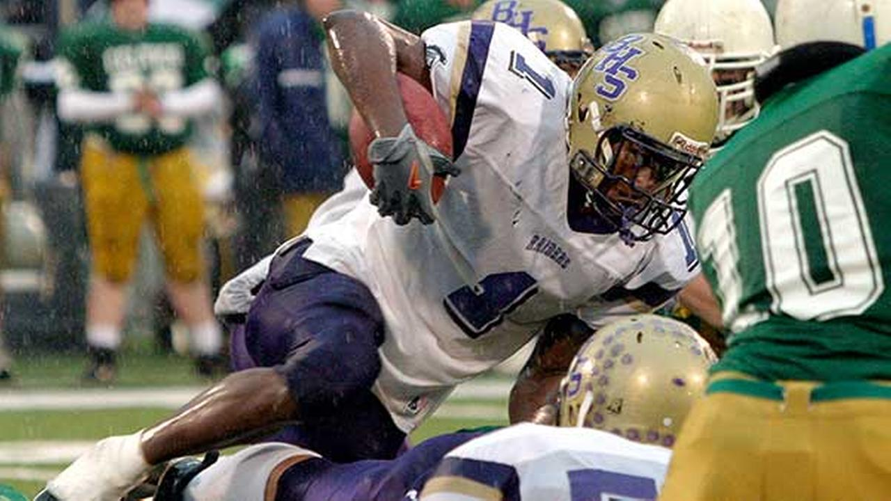 FILE - In this Nov. 27, 2004 file photo, Adrian Arrington, the lead plaintiff in a class-action head injury lawsuit against the NCAA, tries to clear a pile of defenders.