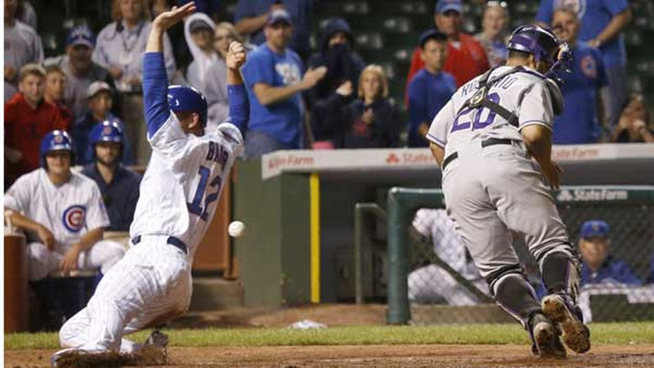 Chicago Cubs John Baker, left, scores the game winning run off a sacrifice fly by Starlin Castro during the 16th inning of a baseball game in Chicago.
