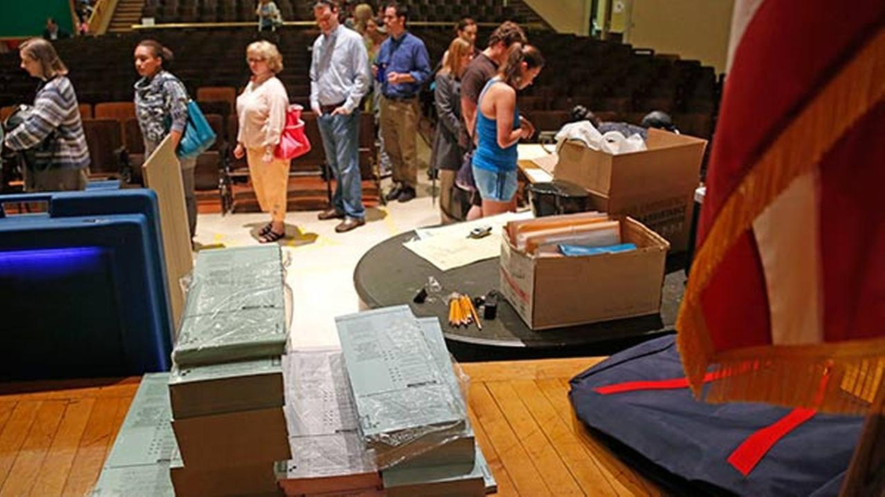 FILE - Voting ballots are stacked and ready as voters wait in line to vote in the Wisconsin recall election June 5, 2012.