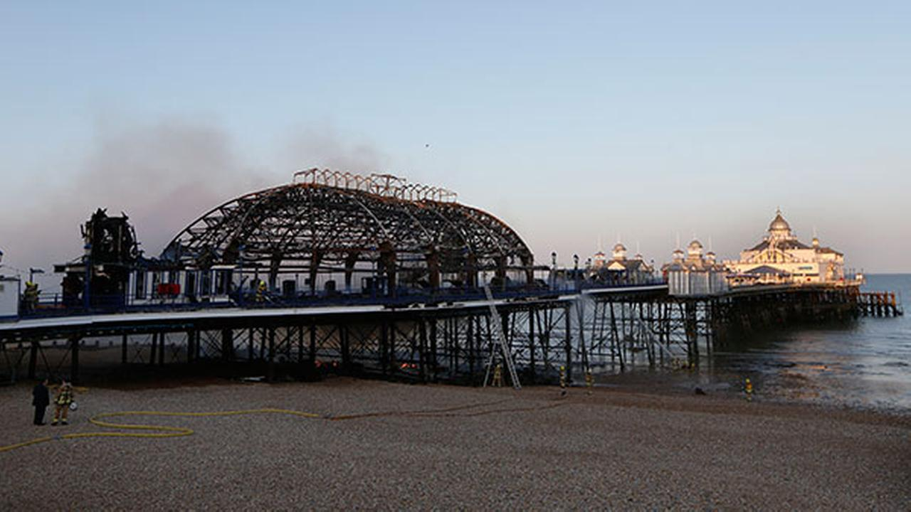 Fire fighters sprays water onto the pier at Eastbourne, England, Wednesday, July 30, 2014 after a fire engulfed the historic and popular attraction and wedding venue.