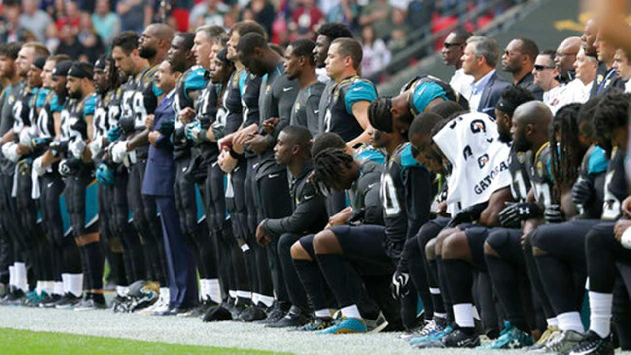 Jacksonville Jaguars players lock arms and kneel down during the playing of the U.S. national anthem before an NFL game against the Baltimore Ravens at Wembley Stadium in London.