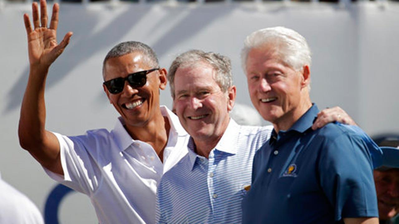 Former U.S. Presidents, from left, Barack Obama, George Bush and Bill Clinton greet spectators at the Presidents Cup at Liberty National Golf Club in Jersey City, N.J.