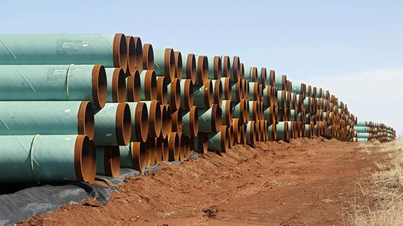 FILE - In this Wednesday, Feb. 1, 2012 file photo, miles of pipe ready to become part of the Keystone Pipeline are stacked in a field near Ripley, Okla.
