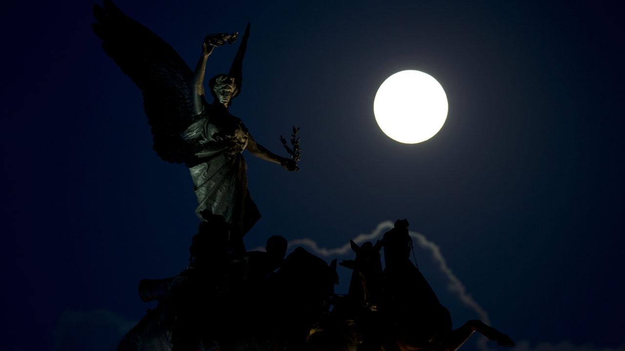 A supermoon appears behind the Angel of Peace sculpture, in London, Sunday, Aug. 10, 2014. AP Photo/Alastair Grant