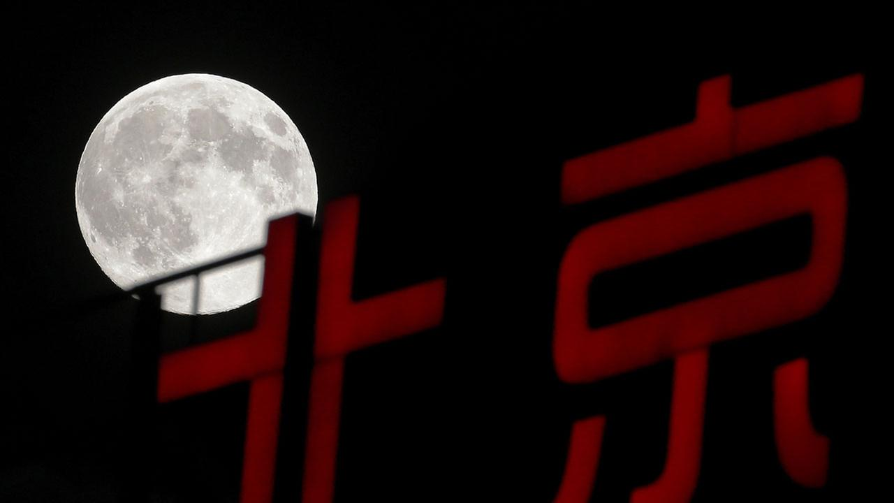 The super moon rises over the Chinese calligraphy on a sign that reads Beijing in Beijing, China, Sunday, August 10, 2014. AP Photo/Andy Wong
