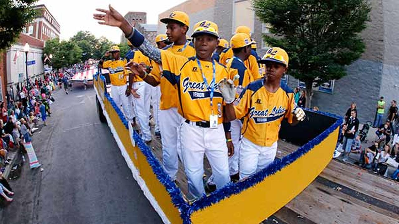 Members of the Jackie Robinson West Little League team from Chicago, Ill., ride in the Little League Grand Slam Parade as it makes its way through downtown Williamsport, PaGene J. Puskar