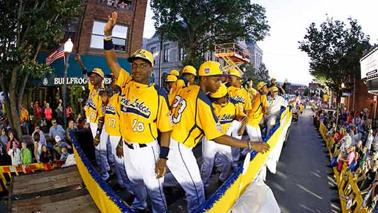 Members of the Jackie Robinson West Little League team from Chicago, Ill., ride in the Little League Grand Slam Parade as it makes its way through downtown Williamsport, Pa.Gene J. Puskar