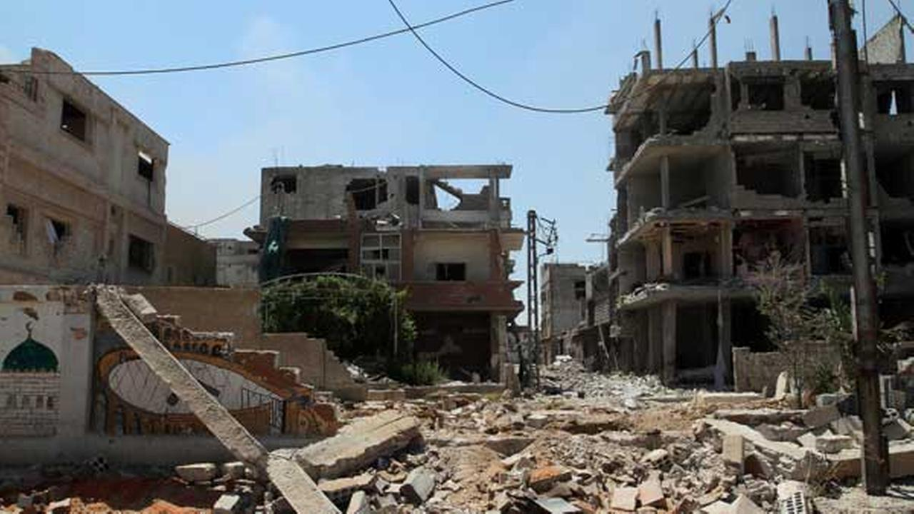 In this photo taken during a Syrian government-led media tour, debris spread around buildings damaged during battles between Syrian troops and rebels in Mleiha.
