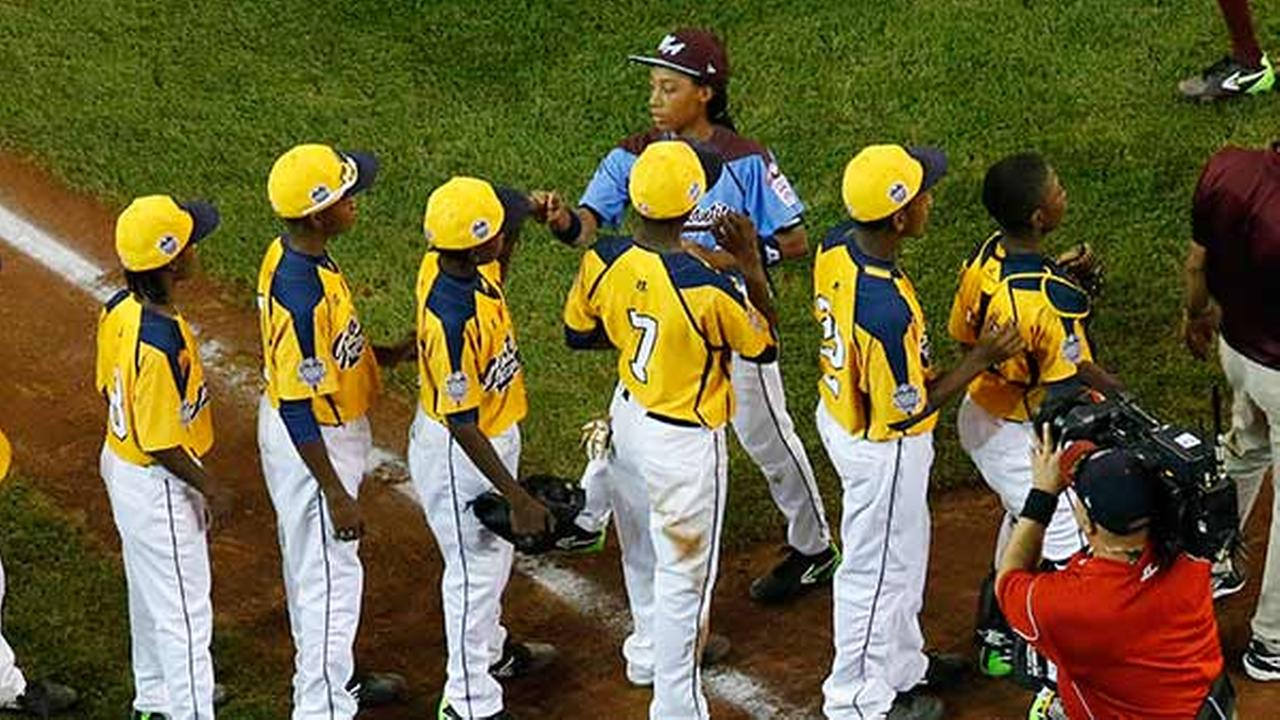 Philadelphias Mone Davis, top center, shakes hands with the players from the Chicago team after Philadelphia lost 6-5 in an elimination baseball game.