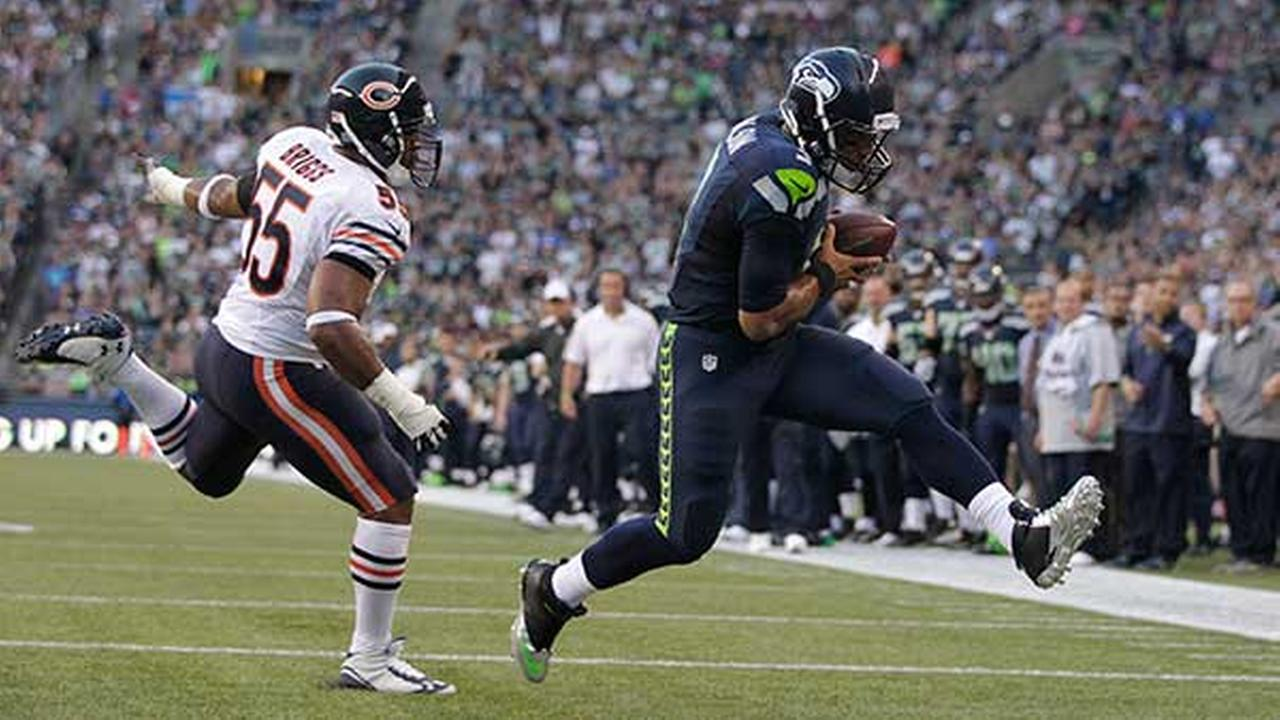 Seattle Seahawks quarterback Russell Wilson, right, scores ahead of Chicago Bears Lance Briggs in the first half of a preseason NFL football game on Aug. 22, 2014, in Seattle.