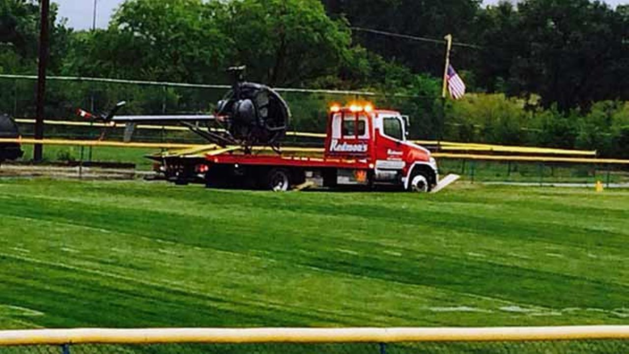 A helicopter is towed after making an emergency landing at a northwest suburban park.