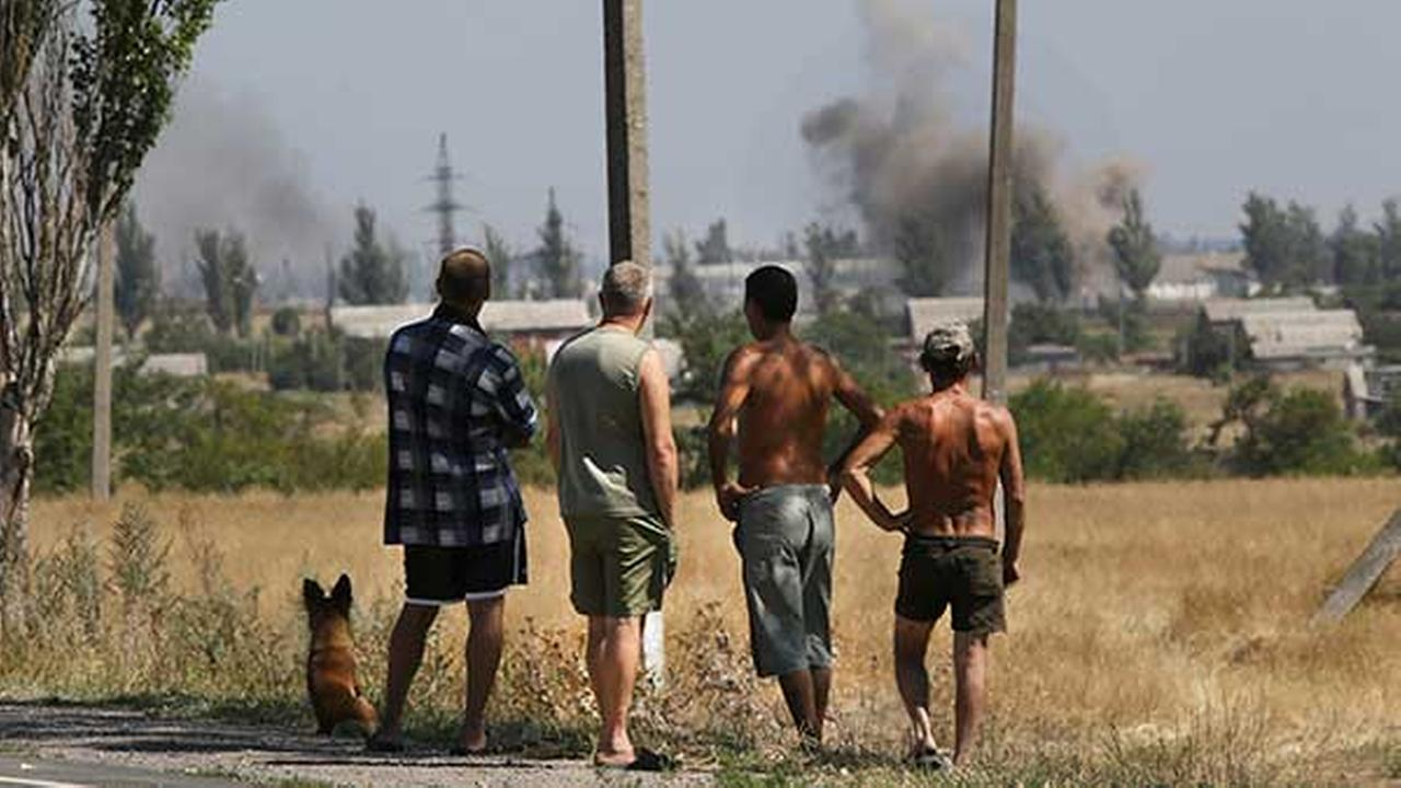 Local residents watch as smoke rises, during shelling, in the town of Novoazovsk, eastern Ukraine on Aug. 27, 2014.