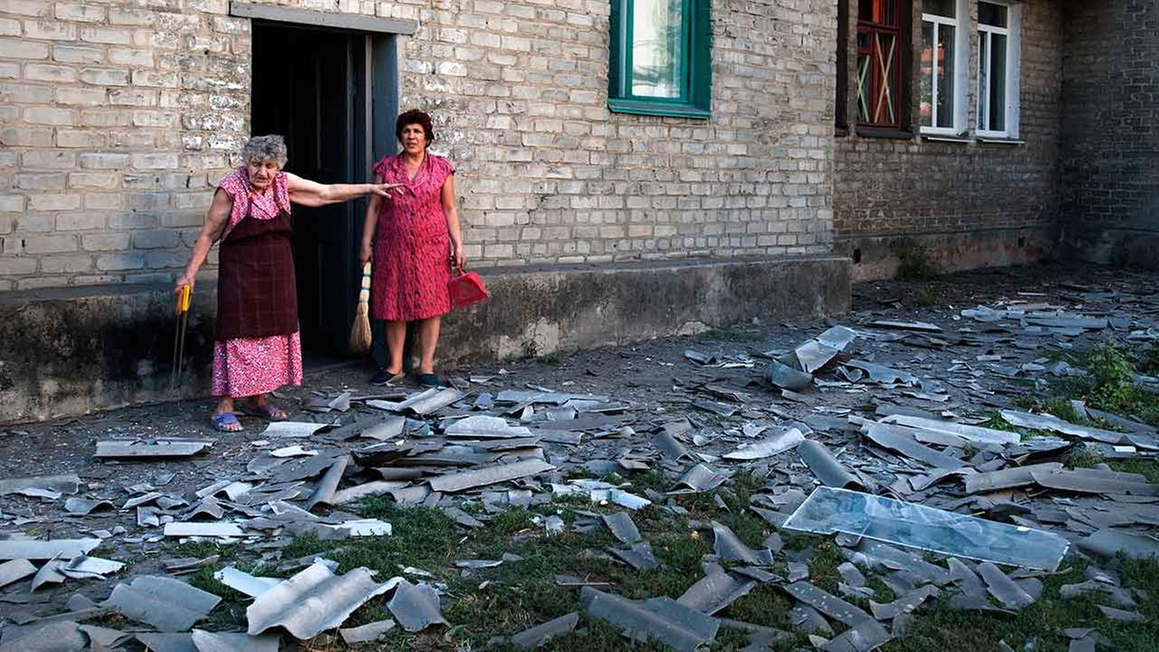 Residents stand near the building where they live after a shelling in Donetsk, eastern Ukraine on August 27, 2014.