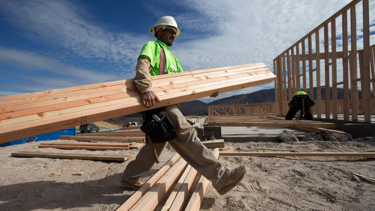 Construction worker Miguel Fonseca carries lumber as he works on a house frame for a new home Friday, Nov. 16, 2012, in Chula Vista, Calif.