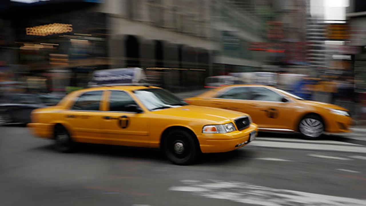 In this Feb. 27, 2014 file photo, New York City taxis drive through New Yorks Times Square.