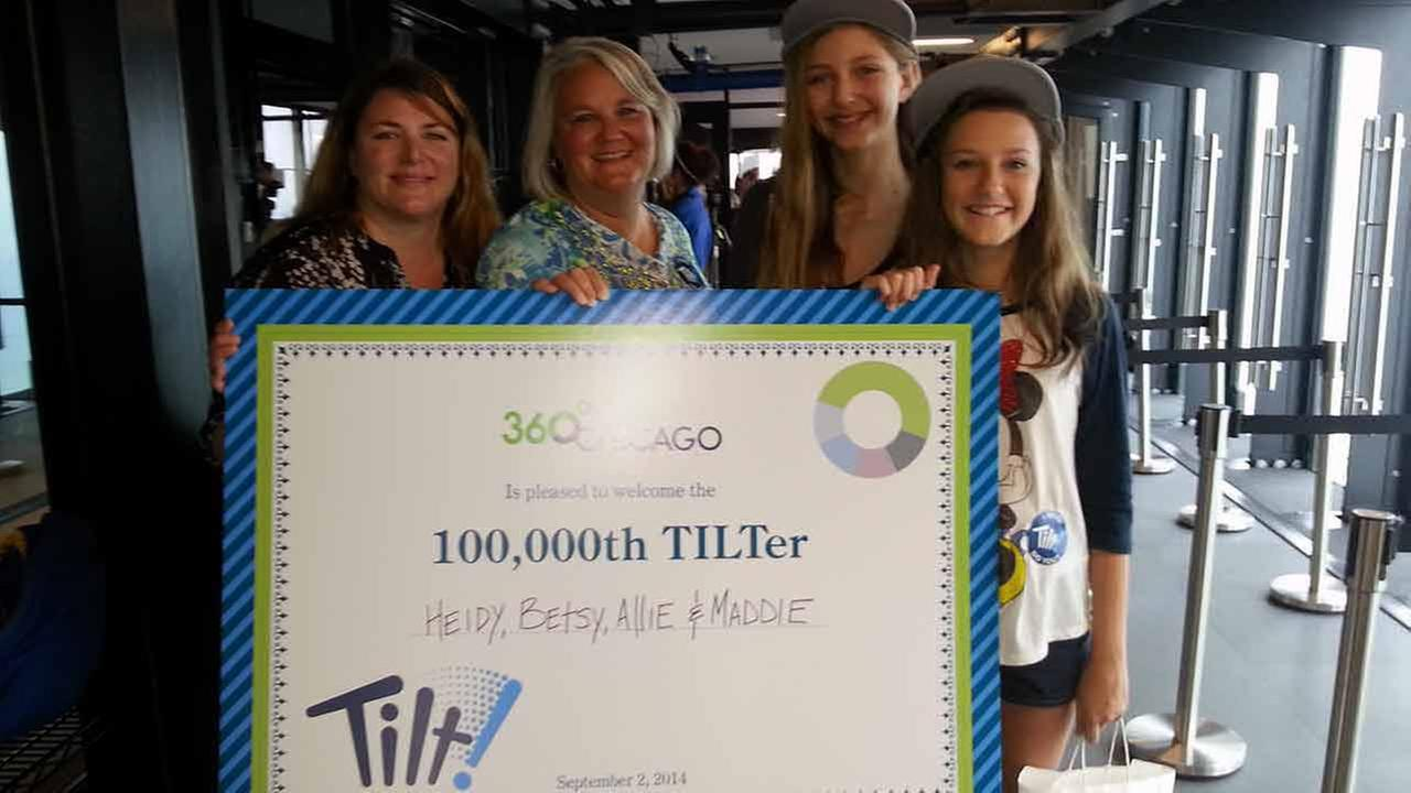 Betsy Harris (41), Heidy Freeman (47), Maddie Harris (12), and Allie Freeman (12), of Lewis Center, Ohio are celebrated as the 100,000th visitors to 360 Chicagos TILT, during a we