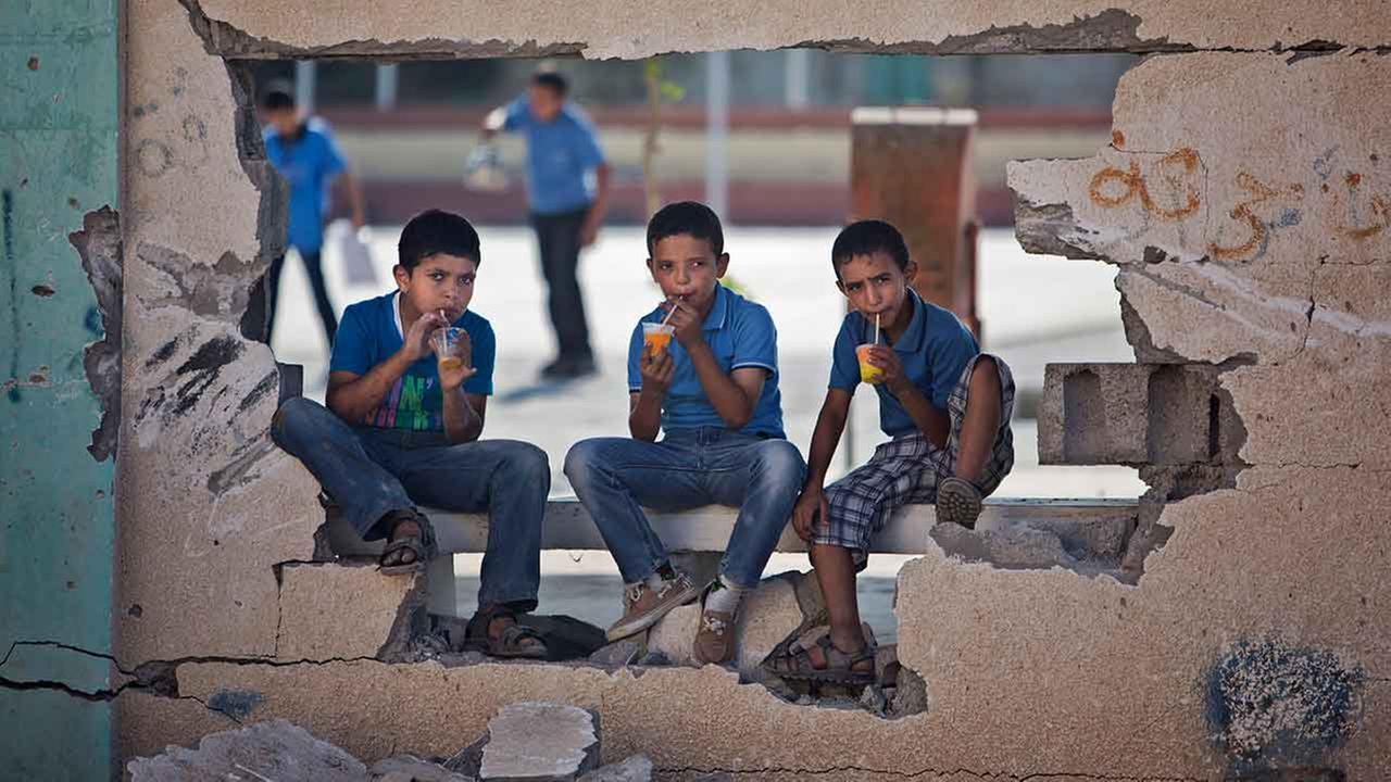 Palestinian school boys drink iced juice as they sit on a damaged wall of a school in Gaza Citys Shijaiyah neighborhood, Sunday, Sept. 14, 2014.