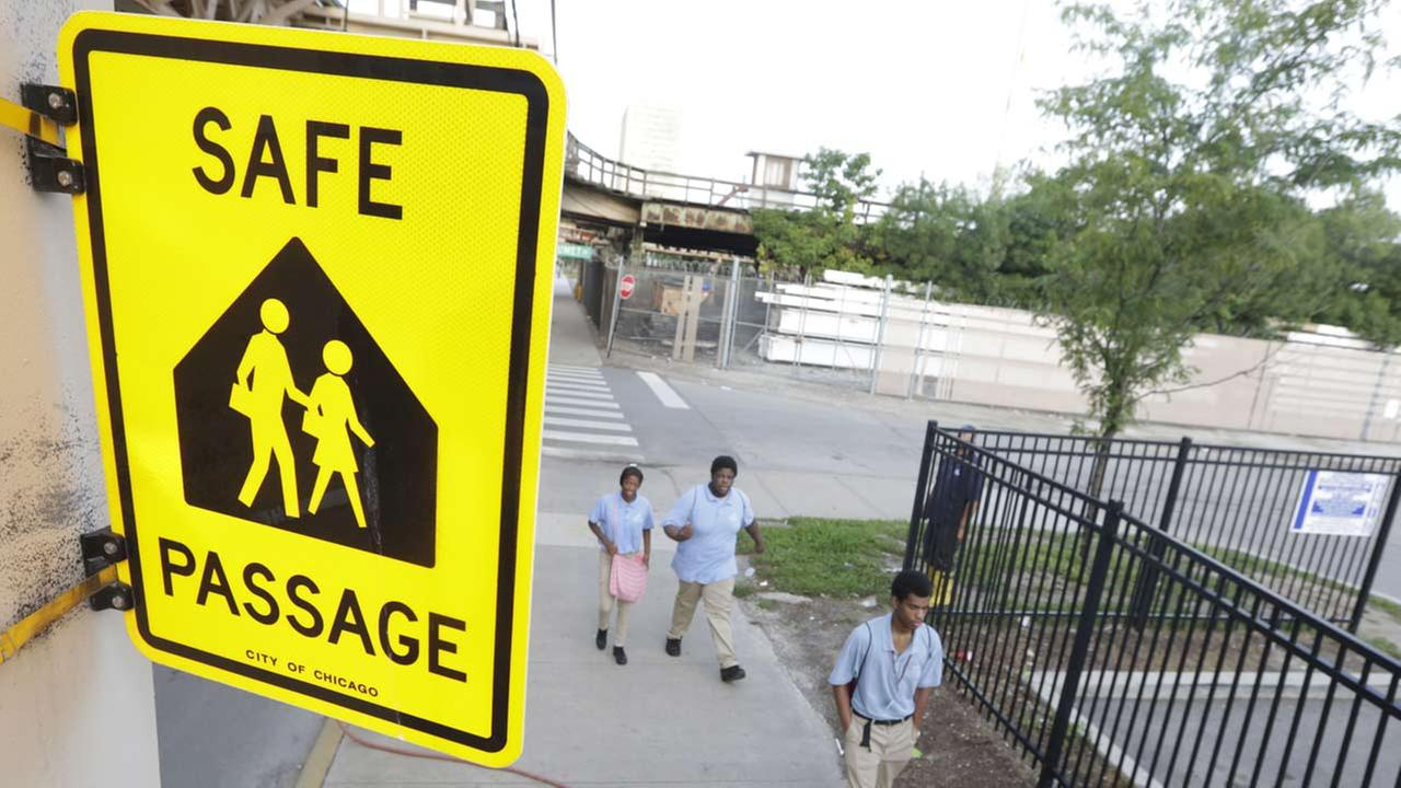 School Children walk a safe passage route along 63rd Street Tuesday, Sept. 2, 2014, in Chicago.