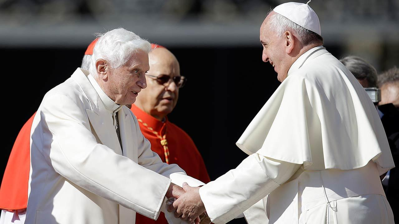 Pope Francis, right, greets Pope Emeritus Benedict XVI at the end of a meeting with elderly faithful in St. Peters Square at the Vatican, Sunday, Sept. 28, 2014.