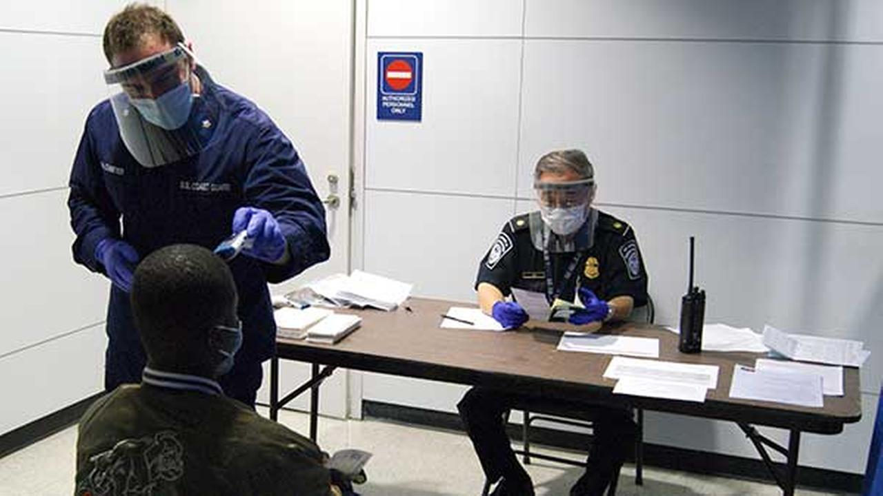 U.S. Coast Guard Health Technician Nathan Wallenmeyer and CBP Supervisor Sam Ko conduct prescreening measures on a passenger arriving from Sierra Leone at OHares Terminal 5.