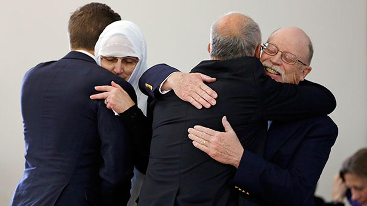 Ed, right, and Paula Kassig, left center, parents of Peter Kassig, are hugged before funeral prayers were held in the mosque at Al-Huda Foundation in Fishers, Ind., Nov. 21, 2014.