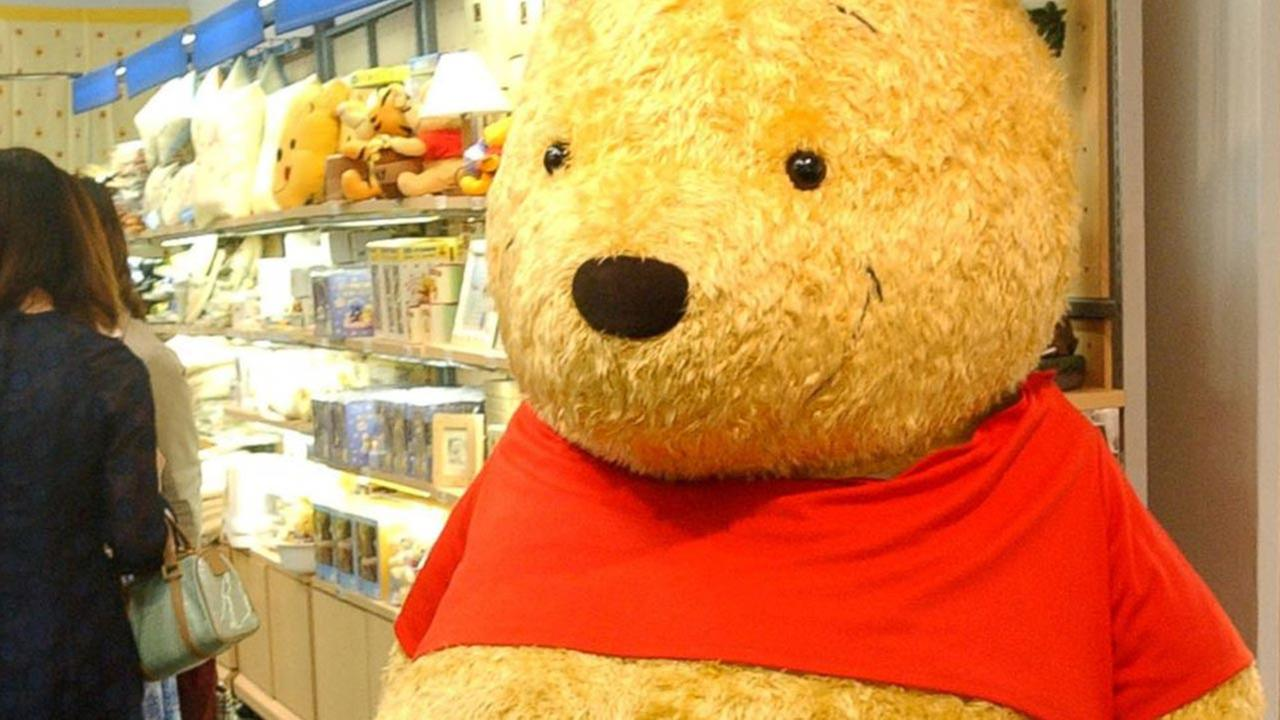 FILE - Two boys chat in front of a giant stuffed doll of Winnie-The-Pooh at the World of Winnie-The-Pooh exhibition at a Tokyo department store in this April 24, 2002 file photo.