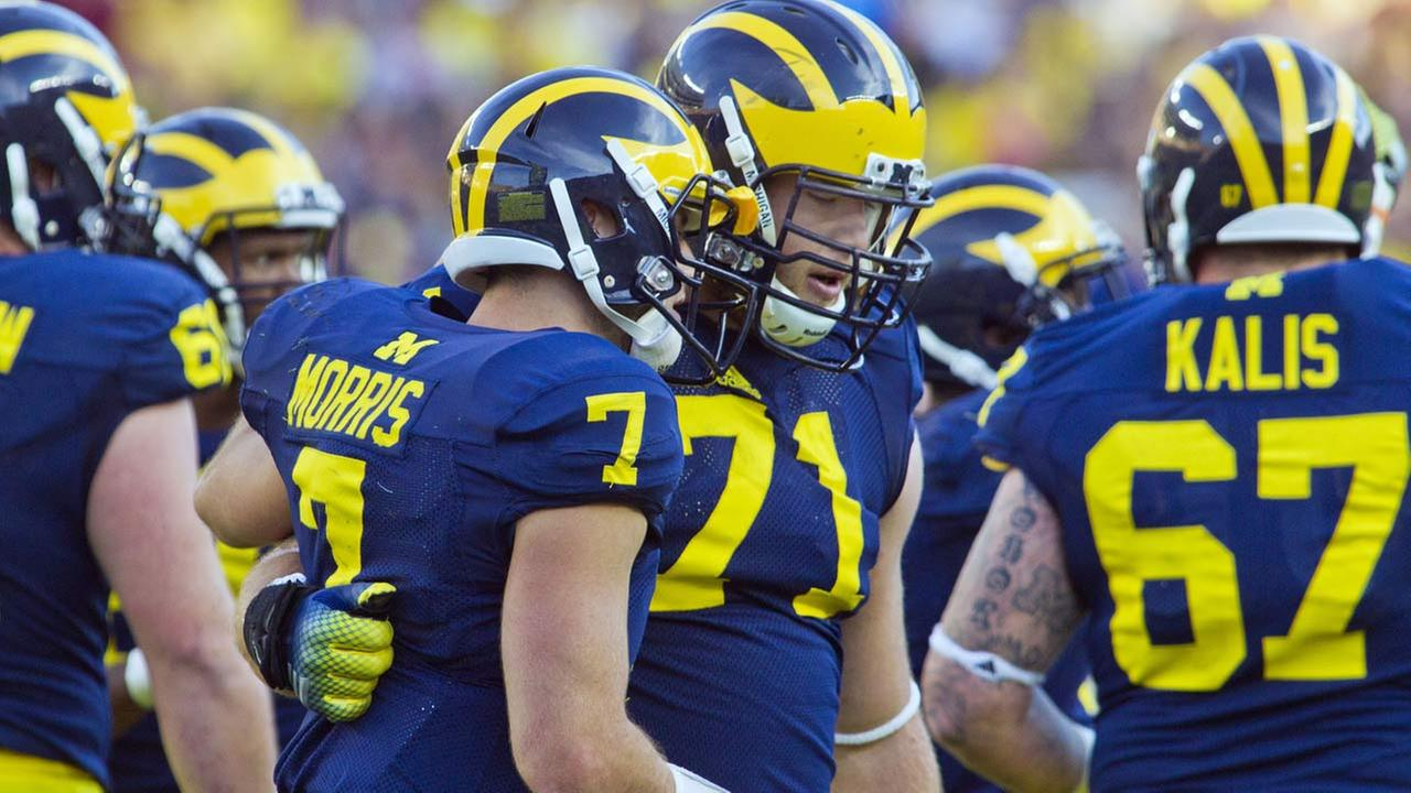 Michigan QB Shane Morris leans against another player after taking a hit on September 30, 2014. (FILE)