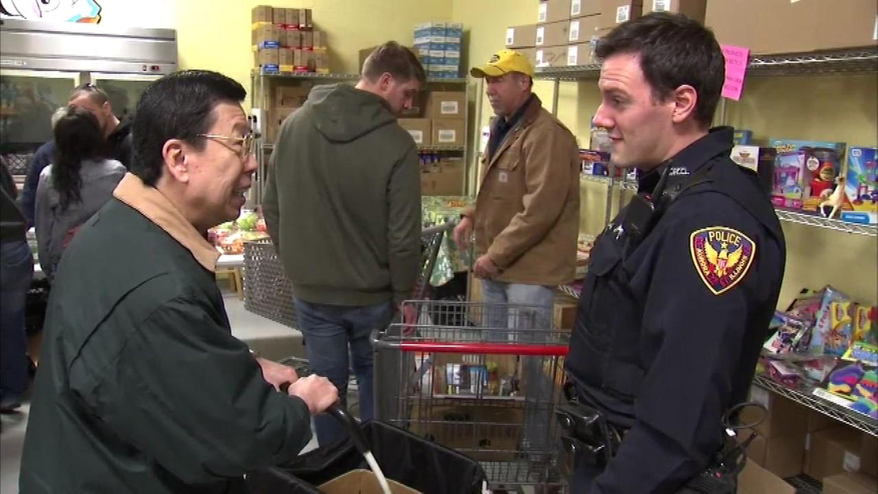 The Aurora Police Department joined the holiday effort to help the less fortunate when officers distributed food at a food pantry on Highland Avenue Friday afternoon.