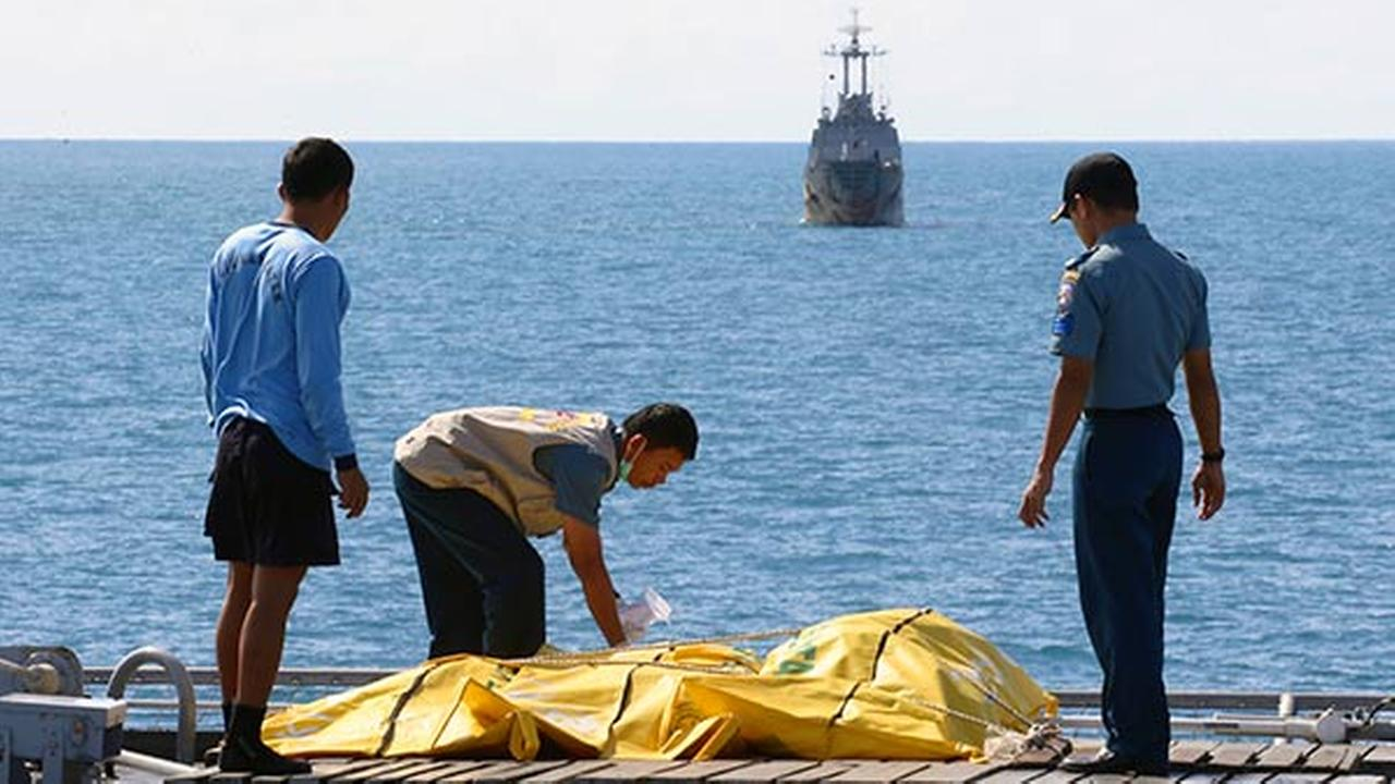 Crews inspect bags containing bodies believed to be victims of AirAsia Flight 8501 on the deck of Indonesian Navy ship KRI Banda Aceh, on the Java Sea, Indonesia on Jan. 23, 2015.