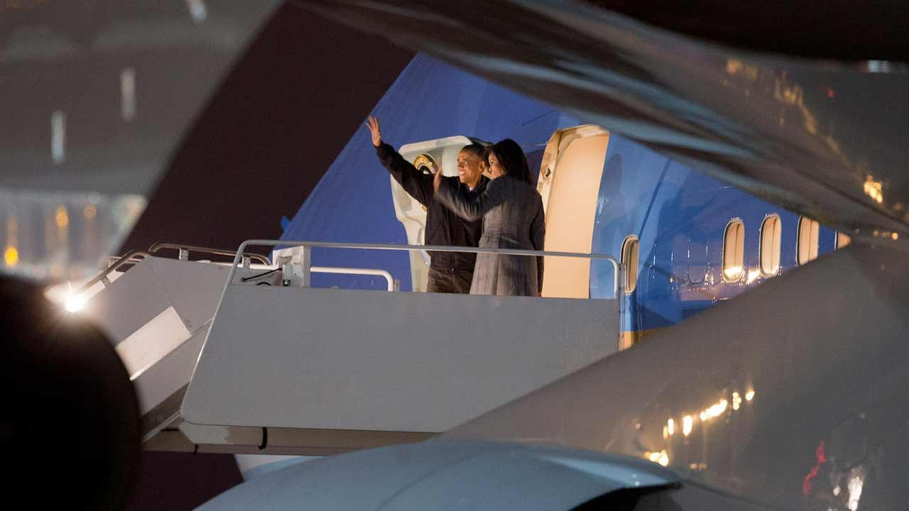 President Barack Obama and first lady Michelle Obama wave as they board Air Force One before departing Andrews Air Force Base, Md., for a trip to India, Saturday, Jan. 24, 2015.