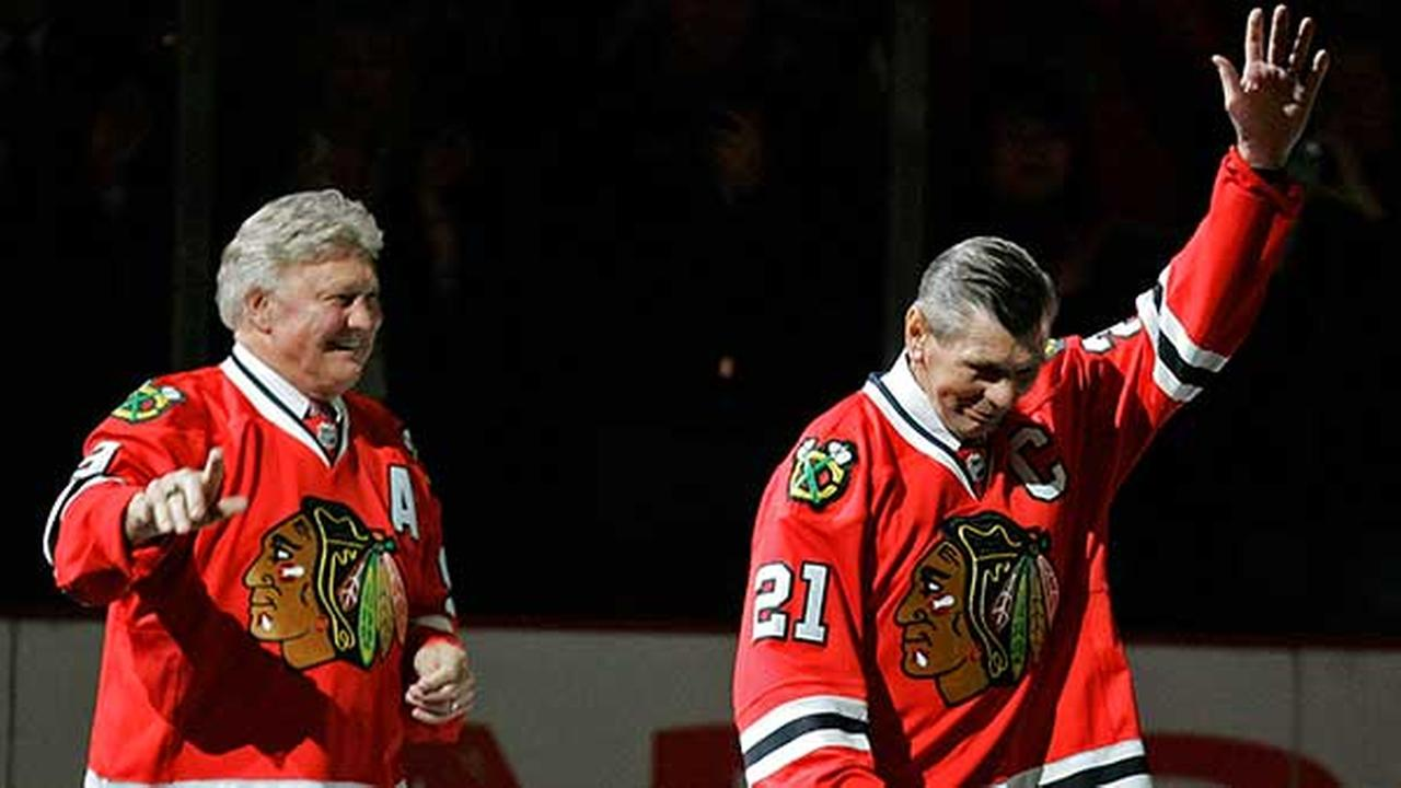 Chicago Blackhawks greats Bobby Hull, left, and Stan Mikita, right, wave to fans as they are introduced before an NHL hockey game on March 7, 2008.