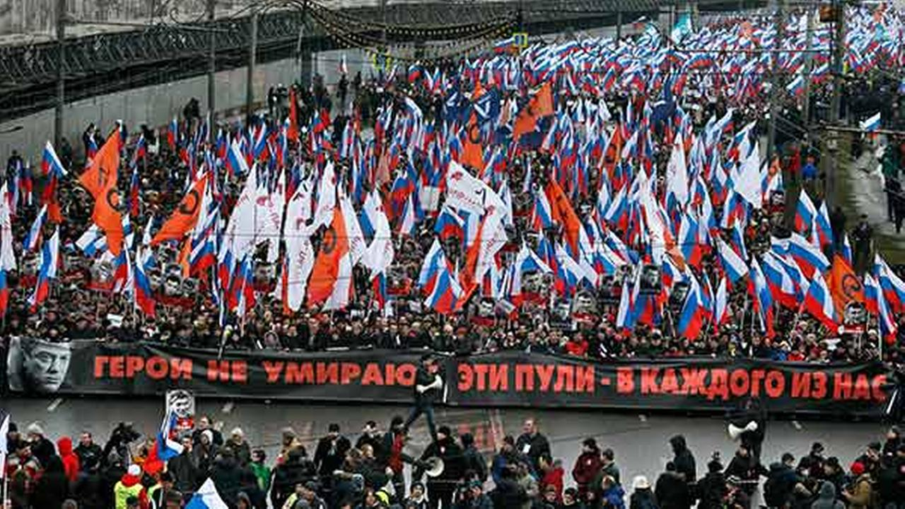 People carry a huge banner reading those bullets for everyone of us, heroes never die! as they march in memory of opposition leader Boris Nemtsov on Sunday, March 1, 2015.