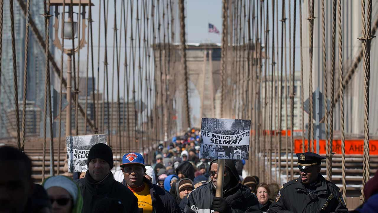 Demonstrators march over the Brooklyn Bridge to mark the 50th anniversary of the landmark event of the civil rights movement in Selma, Ala., on March 7, 2015, in New York.AP Photo/John Minchillo