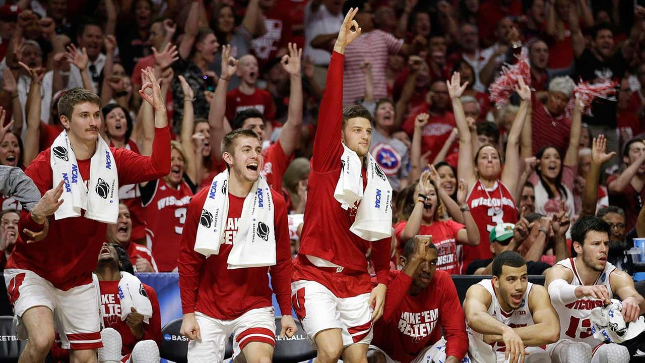 Wisconsin players react after their team made a 3-point basket against Arizona during the second half of a college basketball regional final in the NCAA Tournament.