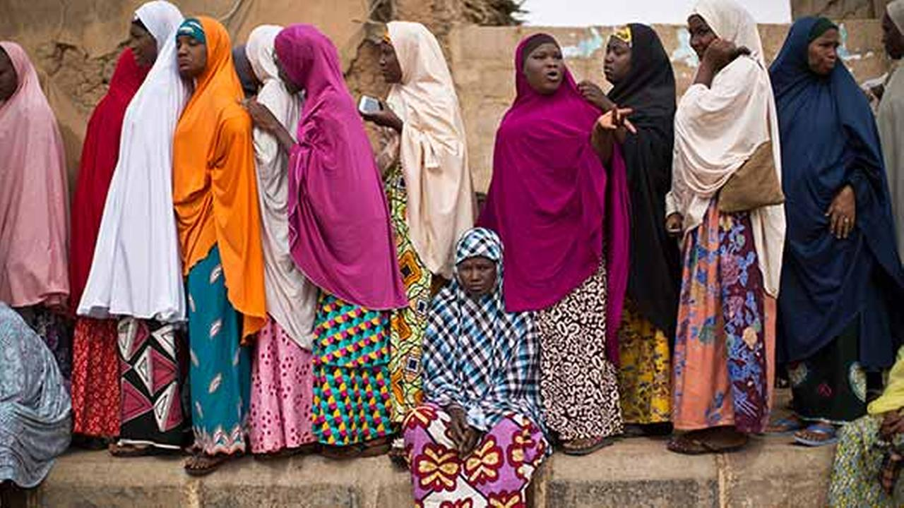 A tired Nigerian woman sits down to rest as others queue, while they face long delays to cast their vote in the afternoon at a polling station in Daura on March 28, 2015.