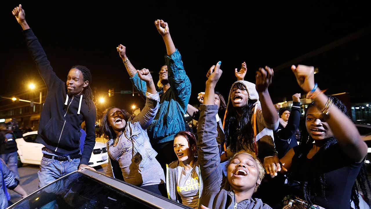 Demonstrators celebrate the announcement of six officers charged in the police-custody death of Freddie Gray before a curfew goes into effect on May 1, 2015, in Baltimore.