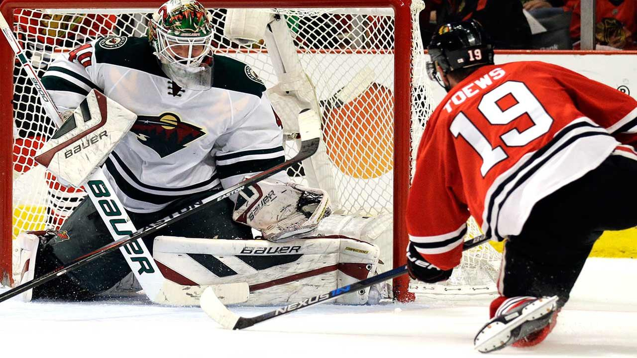 Minnesota Wild goalie Devan Dubnyk, left, fails to stop a shot and goal by Chicago Blackhawks center Jonathan Toews, right, during the second period of Game 2.