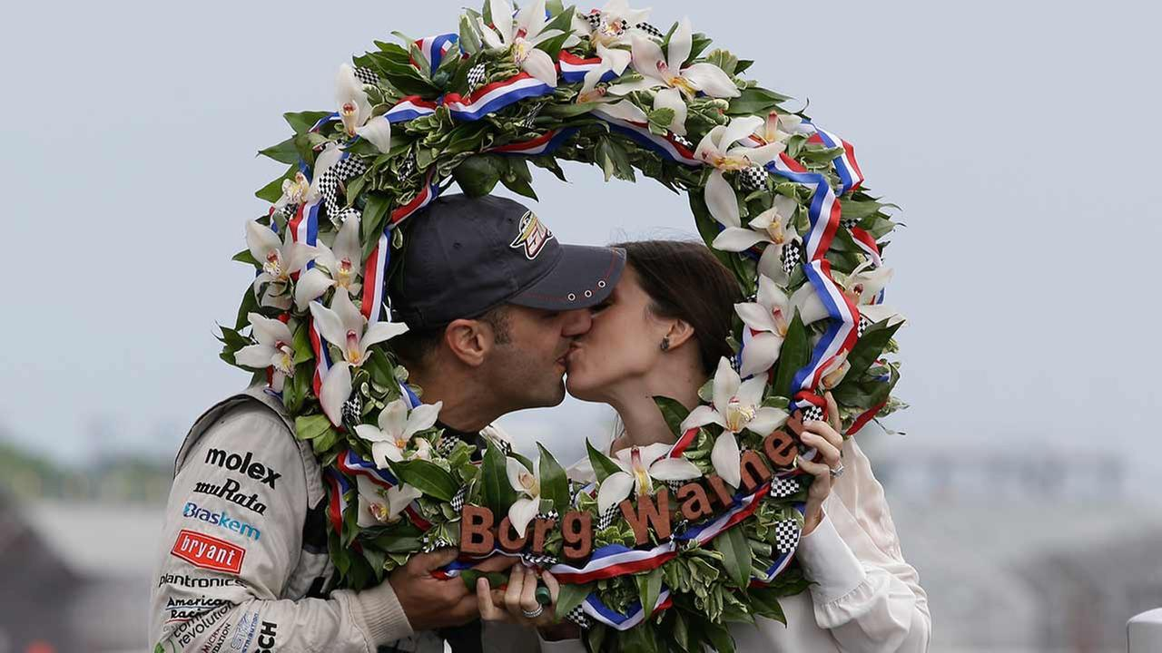 Tony Kanaan, of Brazil, poses with his wife Lauren in the winner wreath after winning the Indianapolis 500 auto race at the Indianapolis Motor Speedway on May 27, 2013.AP Photo/Michael Conroy