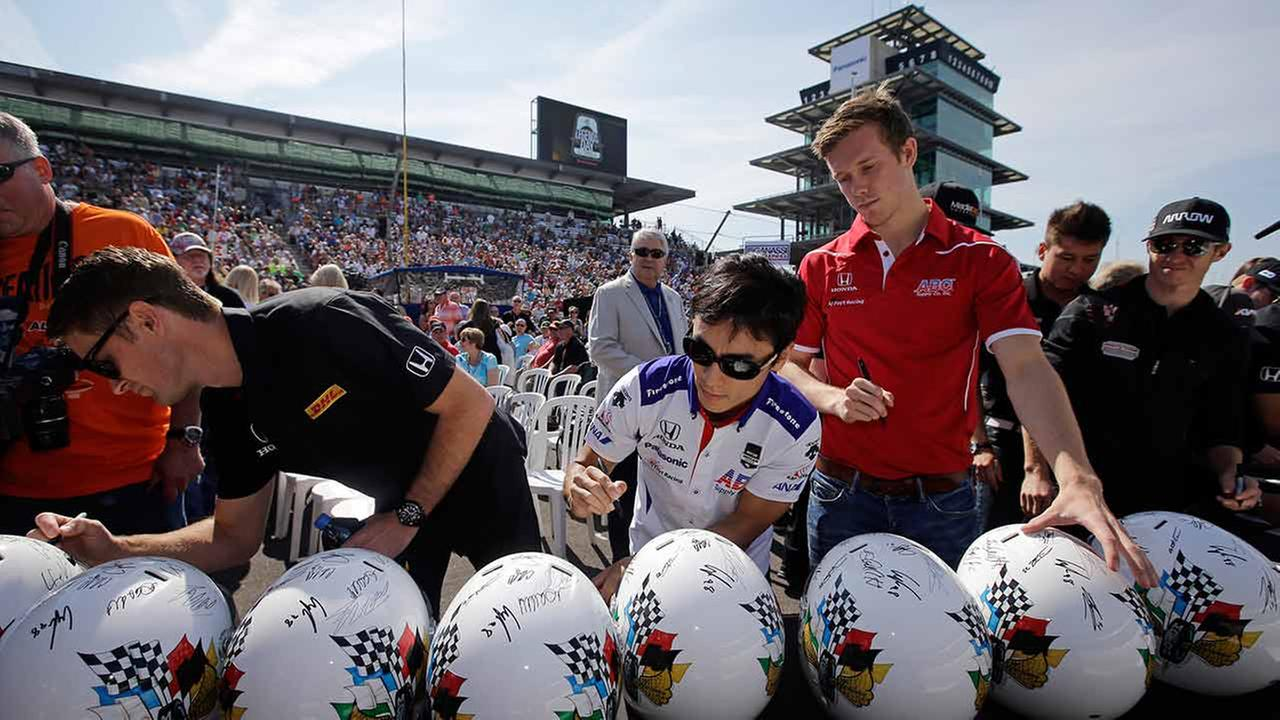 Ryan Hunter-Reay, left, Takuma Sato, of Japan, center, and Jack Hawksworth, of England, signs helmets before the drivers meeting for the Indianapolis 500 on May 23, 2015.AP Photo/Darron Cummings