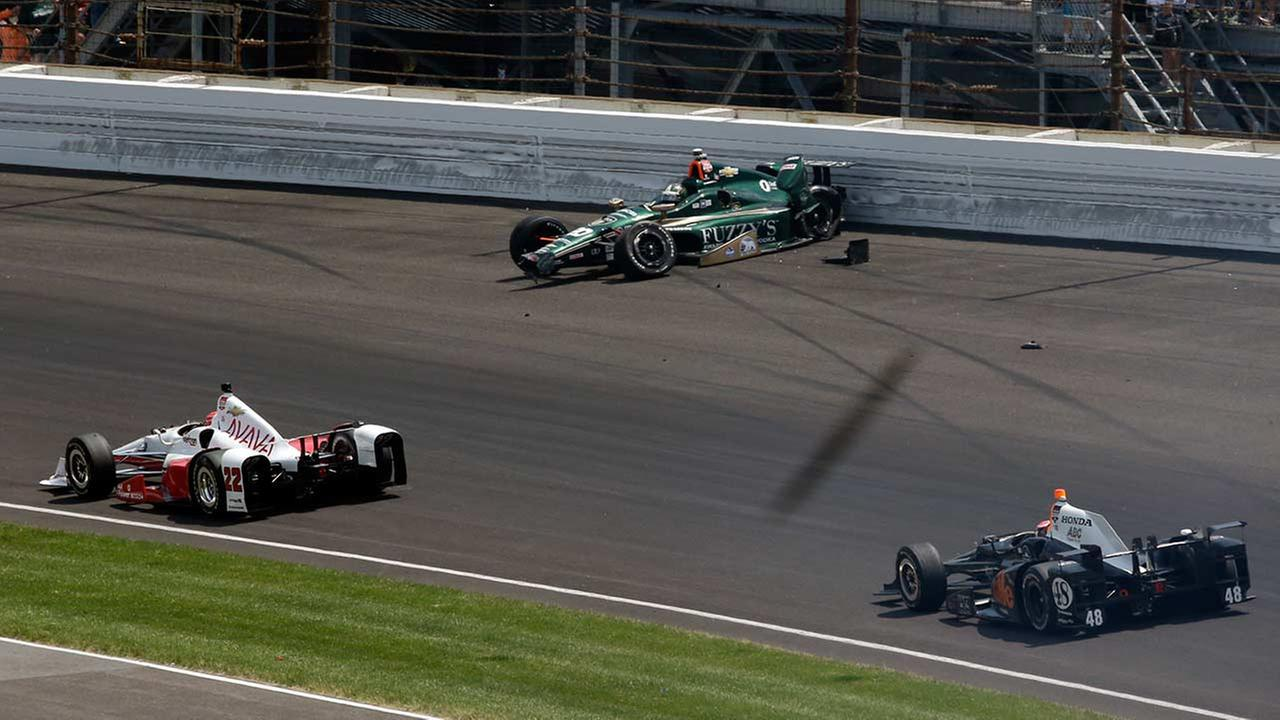 Simon Pagenaud, of France, (22) and Alex Tagliani, of Canada, (48) drive under the crashed car of Ed Carpenter in the first turn during the Indianapolis 500 on May 24, 2015.AP Photo/AJ Mast